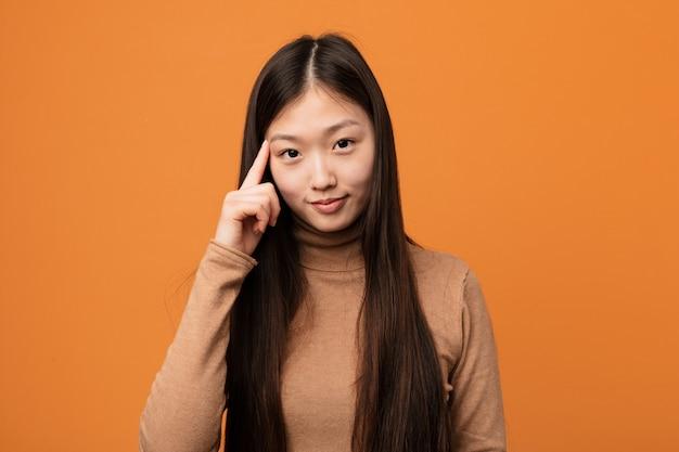 Junge hübsche chinesische frau, die tempel mit dem finger, denkend zeigt, konzentrierte sich auf eine aufgabe.