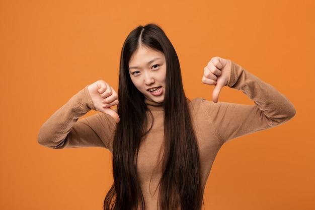 Junge hübsche chinesische frau, die unten daumen zeigt und abneigung ausdrückt.