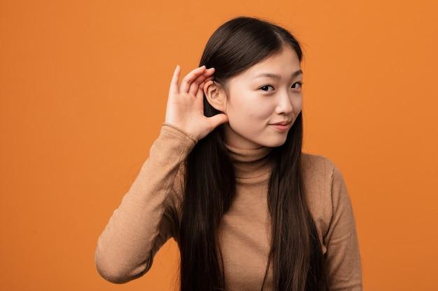 Junge hübsche chinesische frau, die versucht, einen klatsch zu hören.