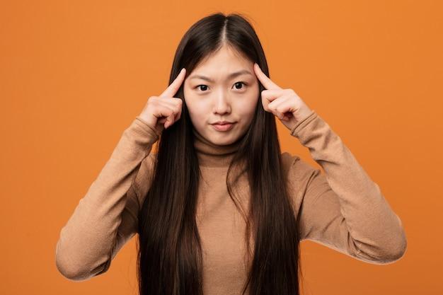 Junge hübsche chinesische frau fokussierte eine aufgabe und hielt ihn zeigefinger, die kopf zeigen.