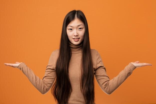 Junge hübsche chinesische frau macht skala mit den armen, fühlt sich glücklich und überzeugt.