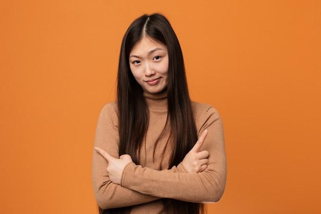 Junge hübsche chinesische frau zeigt seitwärts, versucht, zwischen zwei möglichkeiten zu wählen.