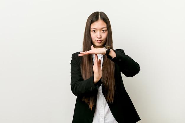 Junge hübsche chinesische geschäftsfrau, die eine auszeitgeste zeigt.