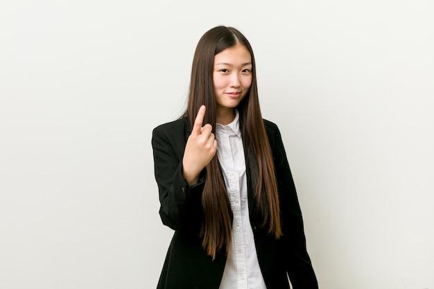 Junge hübsche chinesische geschäftsfrau, die mit dem finger auf sie zeigt, als ob einladung näher kommen.