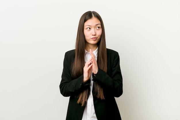 Junge hübsche chinesische geschäftsfrau, die plan im sinn bildet und eine idee aufstellt.