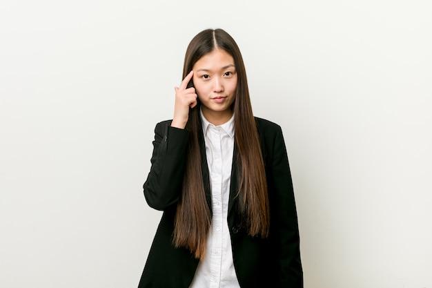 Junge hübsche chinesische geschäftsfrau, die tempel mit dem finger, denkend zeigt, konzentrierte sich auf eine aufgabe.