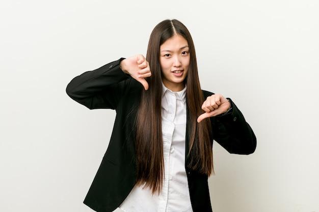 Junge hübsche chinesische geschäftsfrau, die unten daumen zeigt und abneigung ausdrückt.