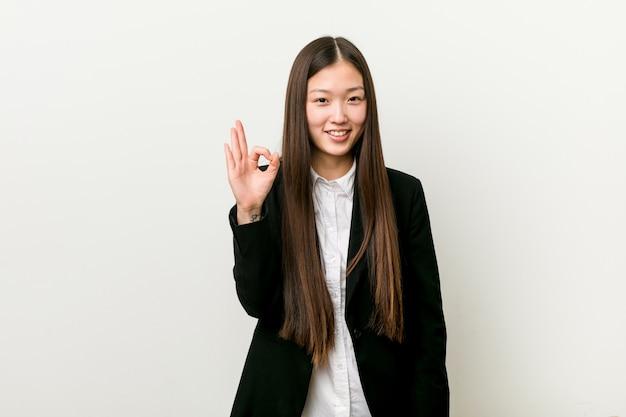 Junge hübsche chinesische geschäftsfrau nett und überzeugt, okaygeste zeigend.