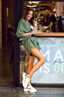 Junge hübsche dame, die freizeit in der stadtcafeteria und in der bar genießt, zitrone trinkt und spaß hat, trendiges hipster-outfit, getönte farben.