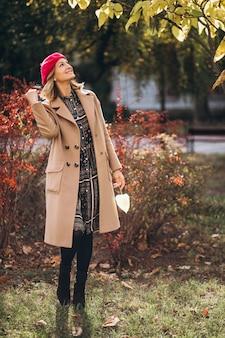 Junge hübsche dame in einem roten barret draußen im park