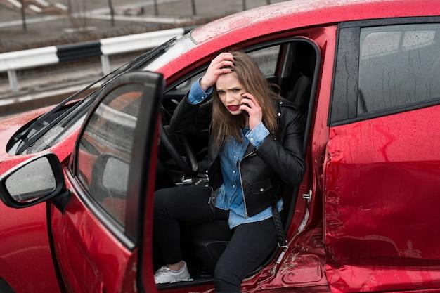 Junge hübsche erschrockene frau im auto. frau ruft rettungsdienst an