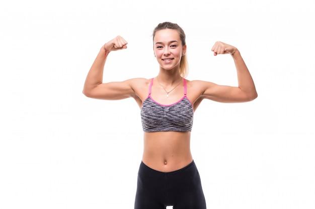 Junge hübsche fitness-dame zeigt ihren muskelstarken körper auf weiß