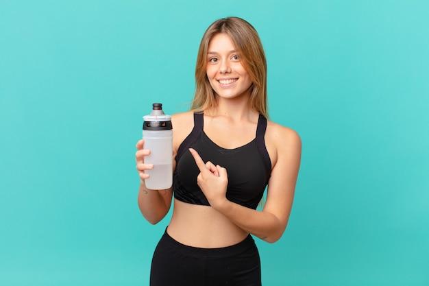 Junge hübsche fitnessfrau, die fröhlich lächelt, sich glücklich fühlt und auf die seite zeigt