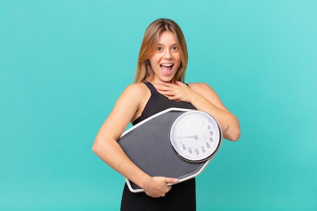 Junge hübsche fitnessfrau lacht laut über einen urkomischen witz