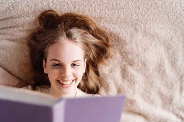 Junge hübsche frau auf dem bett zu hause, das lieblingsbuch genießt