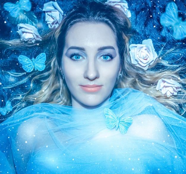 Junge hübsche frau auf mysteriösem waldhintergrund mit blauen schmetterlingen und magischem licht schließen oben