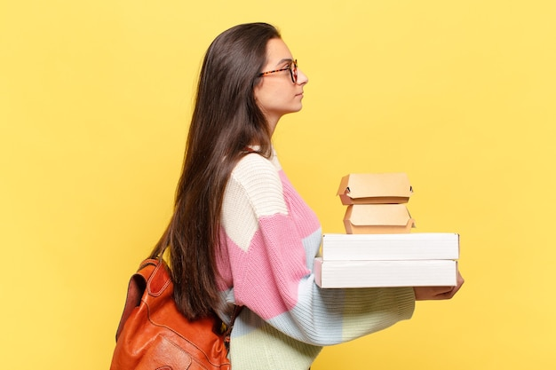 Junge hübsche frau auf profilansicht, die raum voraus kopiert, denkt, sich vorstellt. nehmen sie ein gutes fast-food-konzept