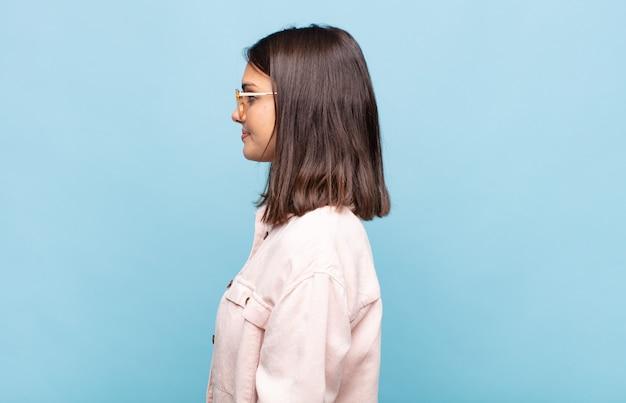 Junge hübsche frau auf profilansicht, die raum voraus kopiert, denkt, sich vorstellt oder träumt