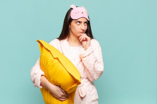 Junge hübsche frau denkt, fühlt sich zweifelhaft und verwirrt, hat verschiedene möglichkeiten und fragt sich, welche entscheidung sie treffen soll. erwachen tragen pyjama-konzept