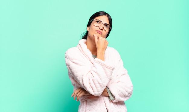 Junge hübsche frau denkt, fühlt sich zweifelhaft und verwirrt, hat verschiedene möglichkeiten und fragt sich, welche entscheidung sie treffen soll. pyjama-konzept