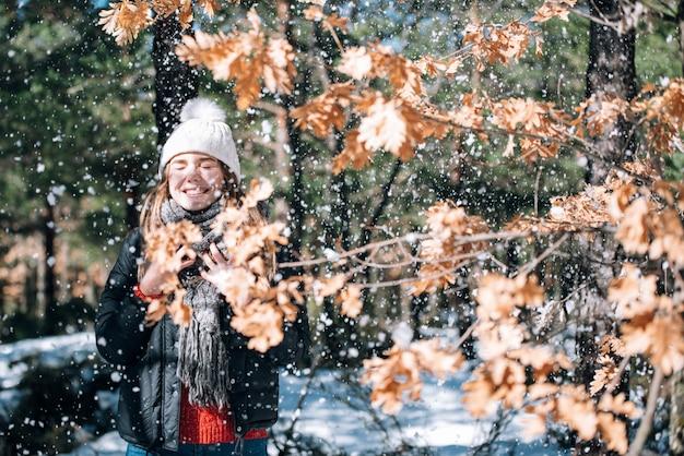 Junge hübsche frau des porträts, die mit schnee im winter genießt und spielt