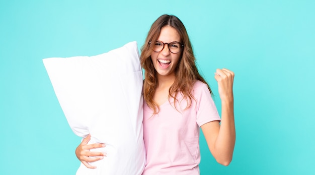 Junge hübsche frau, die aggressiv mit einem wütenden ausdruck schreit, pyjamas trägt und ein kissen hält