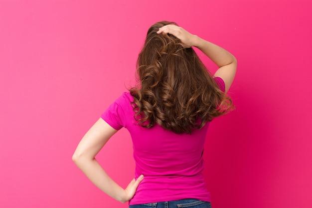 Junge hübsche frau, die ahnungslos und verwirrt fühlt und eine lösung denkt, mit hand auf hüfte und anderen auf kopf, rückansicht gegen rosa wand