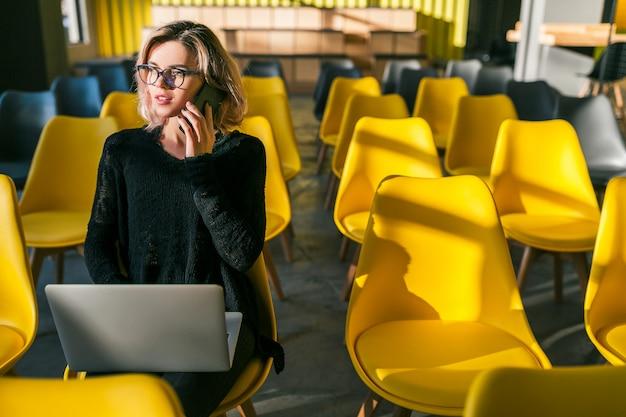 Junge hübsche frau, die allein im mitarbeitenden büro, konferenzraum, viele gelbe stühle sitzt, am laptop, sonnig, hintergrundbeleuchtung arbeitet, am telefon spricht, kommunikation