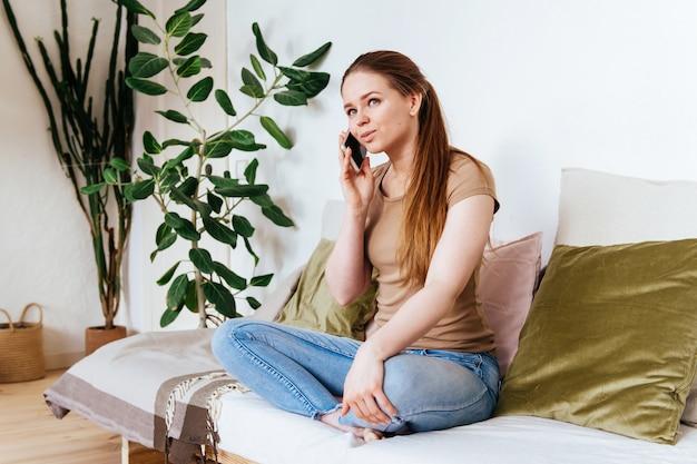 Junge hübsche frau, die am telefon mit freunden und eltern spricht, lächelndes mädchen, das zu hause auf sofa spaßgruß online sitzt