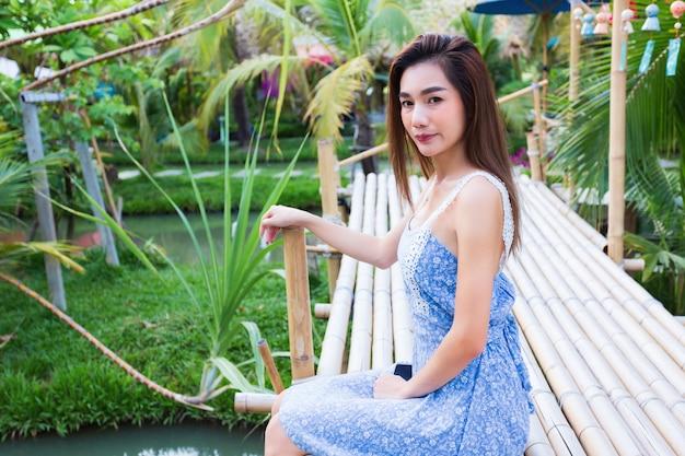 Junge hübsche frau, die auf bambusbrücke im garten sitzt