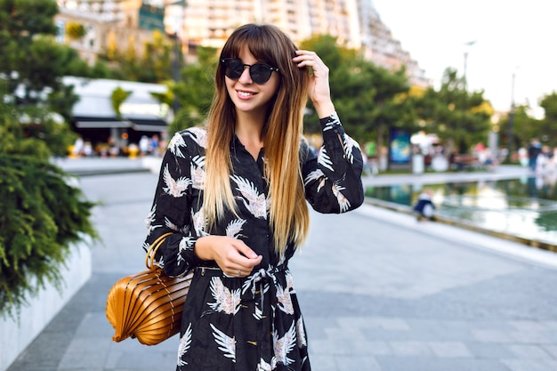 Junge hübsche frau, die auf der straße im stadtzentrum aufwirft, elegantes langes kleid und vintage-stroh-trendtasche trägt, genießen atmosphäre,