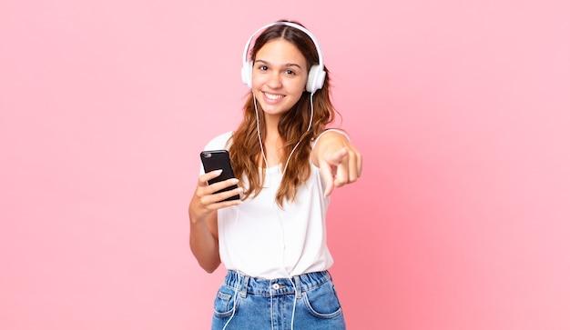 Junge hübsche frau, die auf die kamera zeigt, die sie mit kopfhörern und einem smartphone auswählt