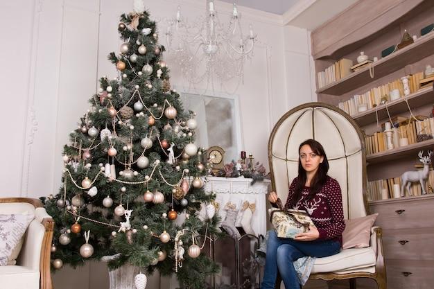 Junge hübsche frau, die auf großen künstlerischen holdinggeschenken sitzt, nahe riesiger weihnachtsbaumdekoration mit verschiedenen verzierungen, während sie die kamera betrachtet.