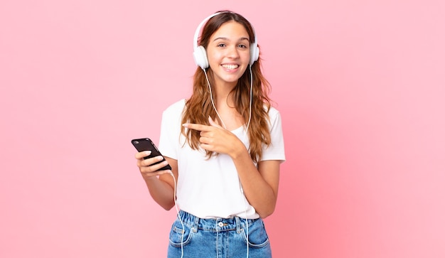 Junge hübsche frau, die aufgeregt und überrascht aussieht und mit kopfhörern und einem smartphone auf die seite zeigt