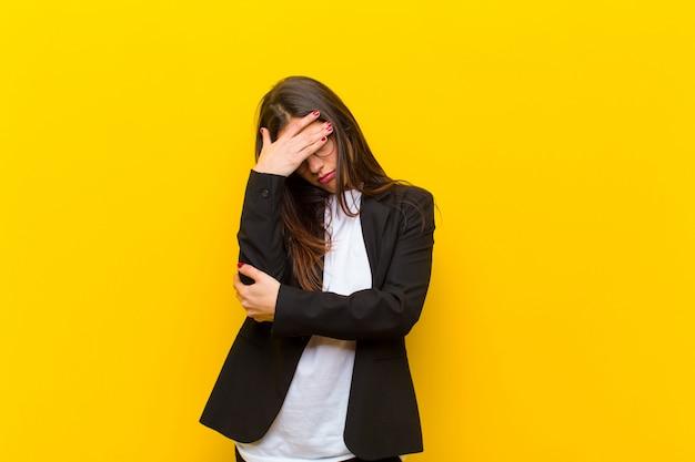 Junge hübsche frau, die betont, beschämt oder, mit kopfschmerzen, gesicht mit der hand gegen orange wand bedeckend gestört schaut