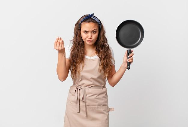 Junge hübsche frau, die capice oder geldgeste macht, ihnen sagt, dass sie das kochkonzept bezahlen und eine pfanne halten sollen