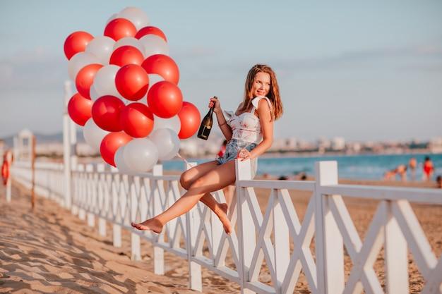 Junge hübsche frau, die champagner und glas hält, sitzt auf einem zaun am strand gegen luftballons und meer