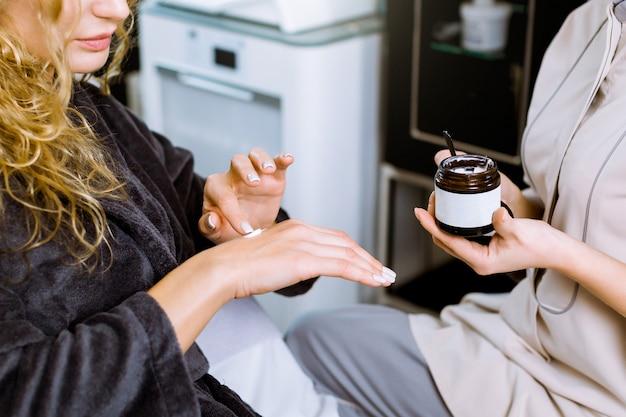Junge hübsche frau, die creme auf hand sitzt, die im modernen kosmetik- und spa-salon sitzt. ärztin kosmetikerin hält creme im dunklen glas.