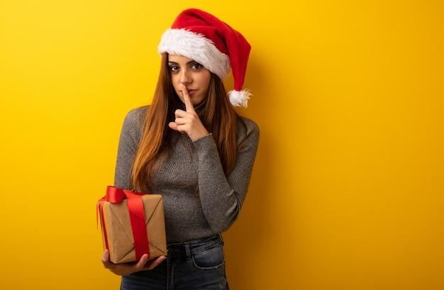 Junge hübsche frau, die das geschenk hält, das ein geheimnis hält oder um ruhe bittet