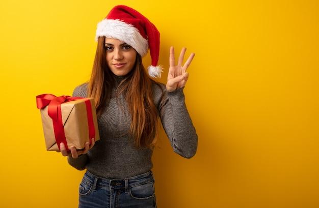 Junge hübsche frau, die das geschenk zeigt nr. drei hält