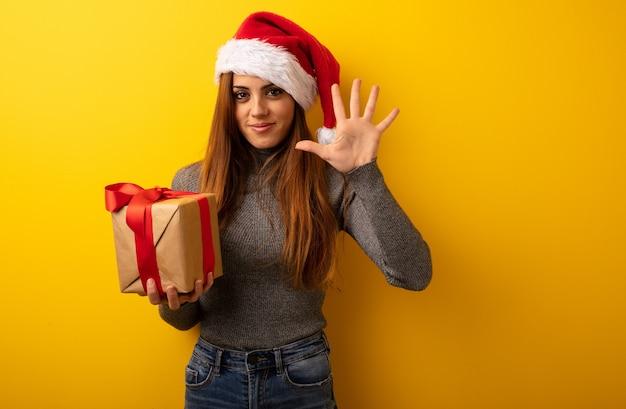 Junge hübsche frau, die das geschenk zeigt nr. fünf hält