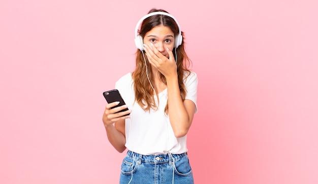 Junge hübsche frau, die den mund mit den händen bedeckt, mit einem schockierten mit kopfhörern und einem smartphone