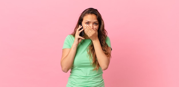 Junge hübsche frau, die den mund mit den händen mit einem schockierten bedeckt und ein smartphone hält
