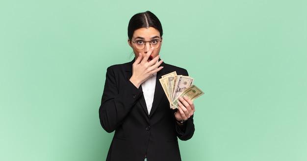 Junge hübsche frau, die den mund mit den händen mit einem schockierten, überraschten ausdruck bedeckt, ein geheimnis hält oder oops sagt. geschäfts- und banknotenkonzept