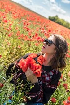 Junge hübsche frau, die die sommerzeit im mohnblumenfeld genießt. freiheit