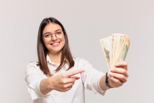 Junge hübsche frau, die dollarbanknoten zeigt oder zeigt und hält