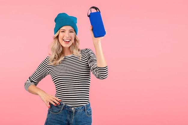 Junge hübsche frau, die drahtlosen lautsprecher hält, der musik trägt, die gestreiftes hemd und blauen hut trägt, der glückliche positive stimmung lächelt, die auf rosa hintergrund lokalisiert aufwirft