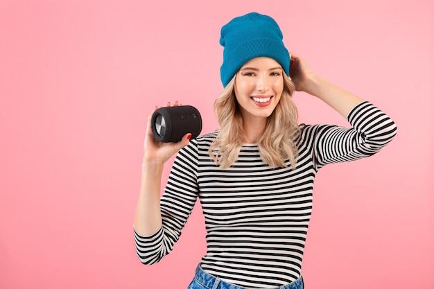 Junge hübsche frau, die drahtlosen lautsprecher hält, der musik trägt, die gestreiftes hemd und blauen hut trägt, der glückliche positive stimmung lächelt, die auf rosa wand isoliert aufwirft