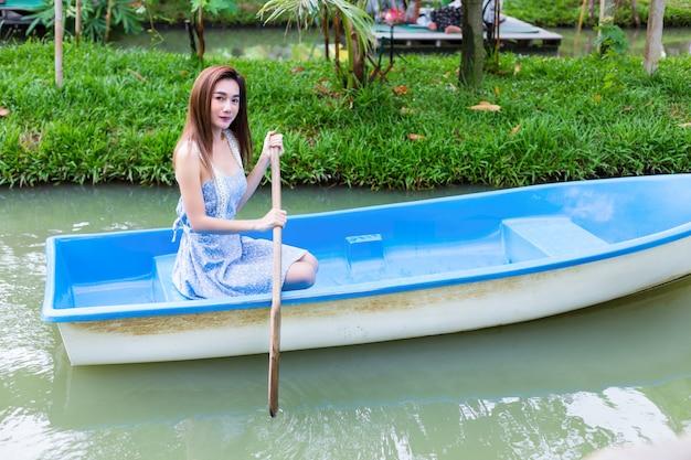Junge hübsche frau, die durch paddelboot sich entspannt