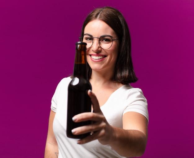 Junge hübsche frau, die ein bier trinkt